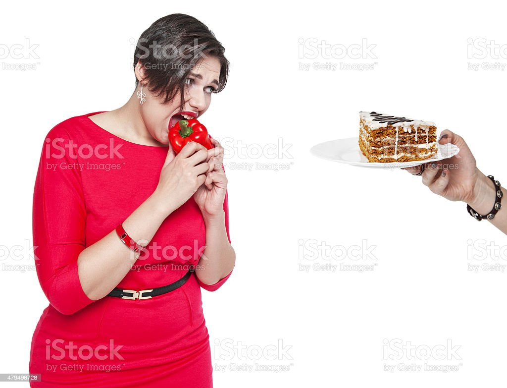 Plus size woman making choice between healthy and unhealthy food stock photo