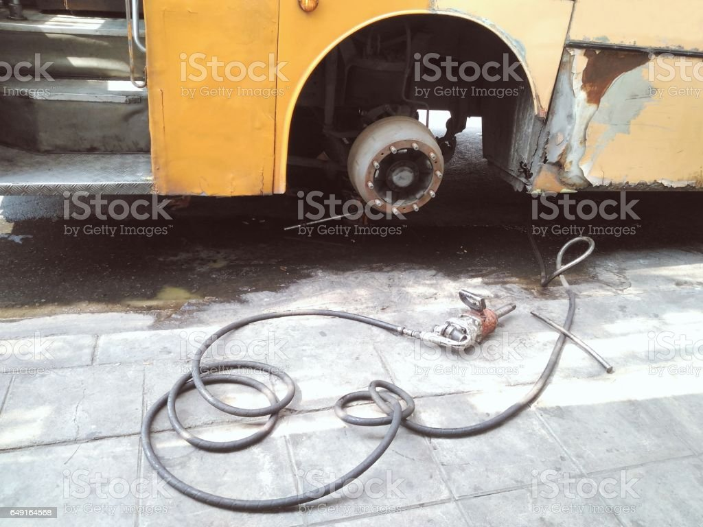 Pneumatic gun for bolt tightening, old dirty bus tire replacement stock photo