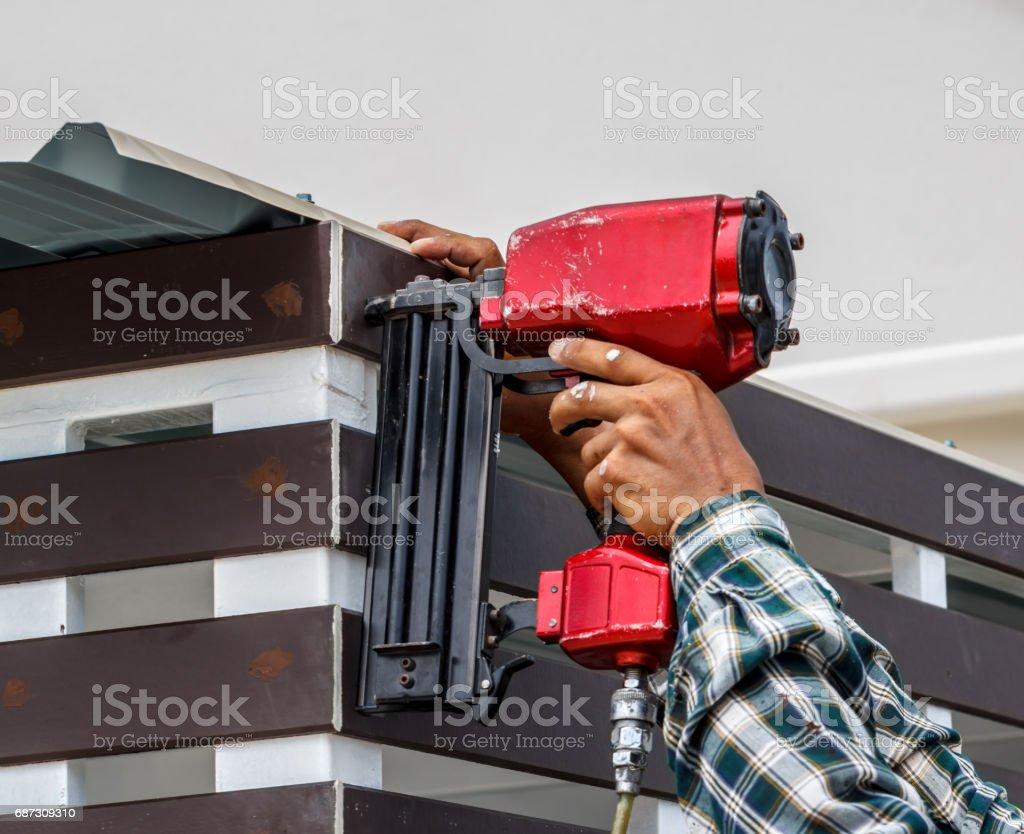 Pneumatic nails gun shooting stock photo