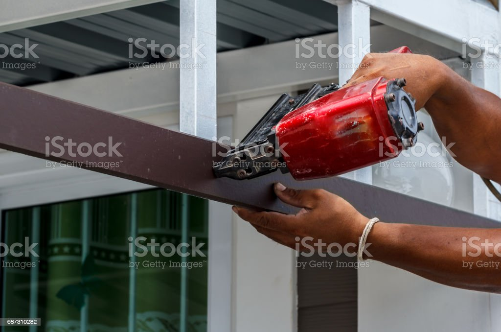 Pneumatic nails gun shooting stock photo