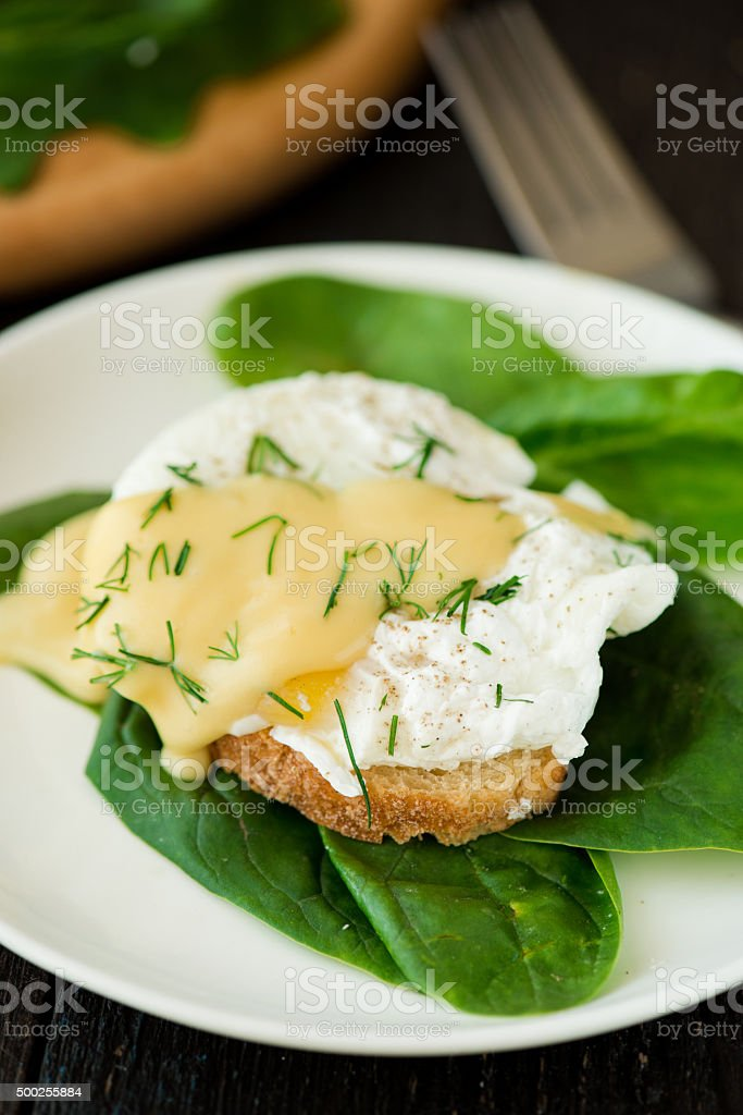 Poached egg on a piece of bread with spinach stock photo