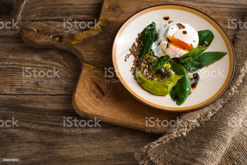 Poached egg with avocado cream and spinach on twooden table stock photo