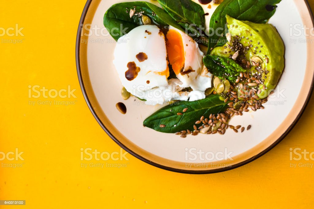 Poached egg with avocado cream and spinach on yellow background stock photo