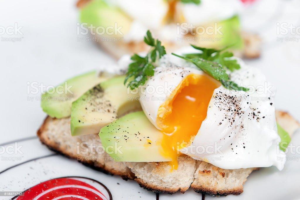 Poached egg with avocado on white bread. stock photo