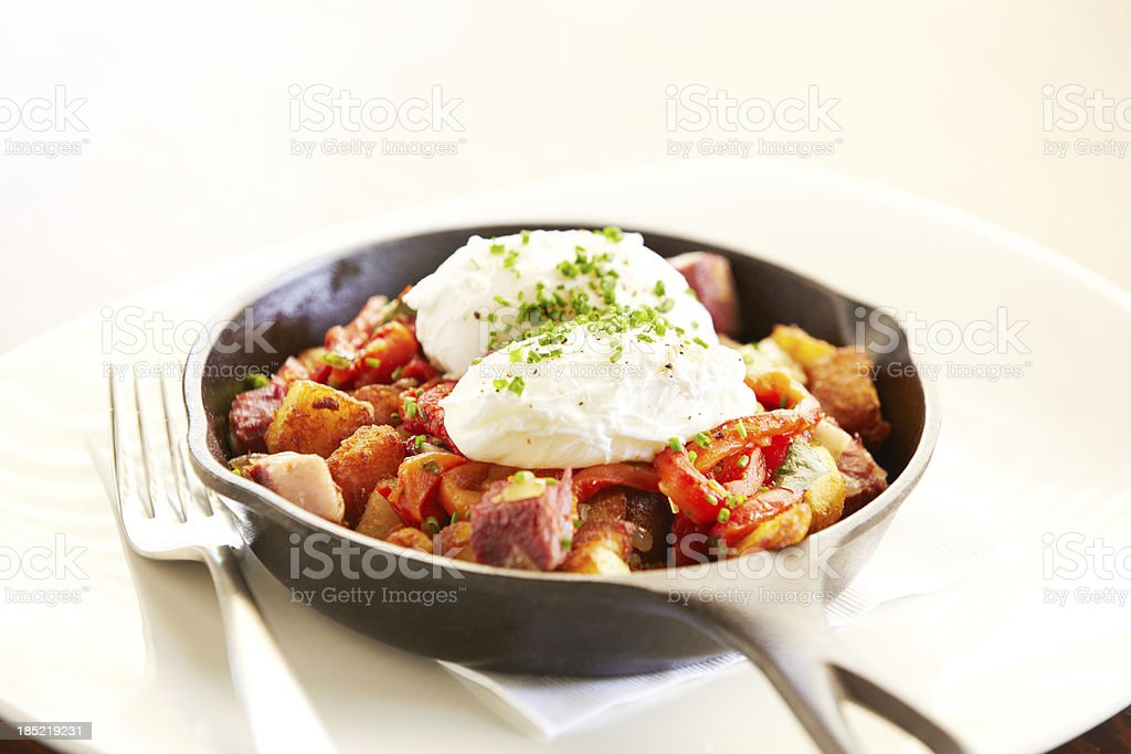 Poached eggs on top of potatoes in iron skillet royalty-free stock photo