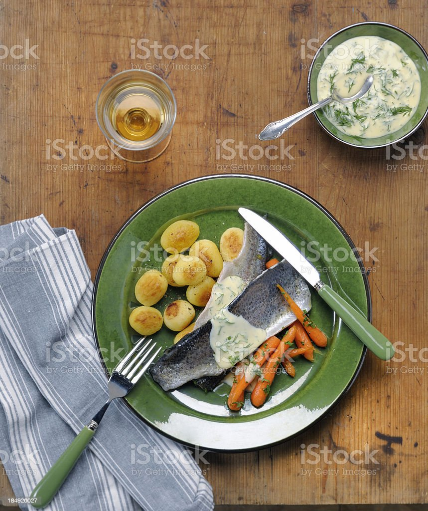 poached trout fillet with dille sauce, carrots and baked potatoes stock photo