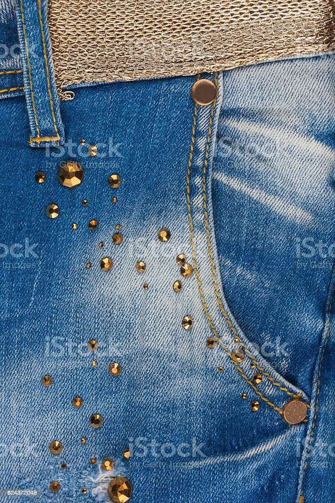 Pocket jeans with rhinestones and gold belt. stock photo