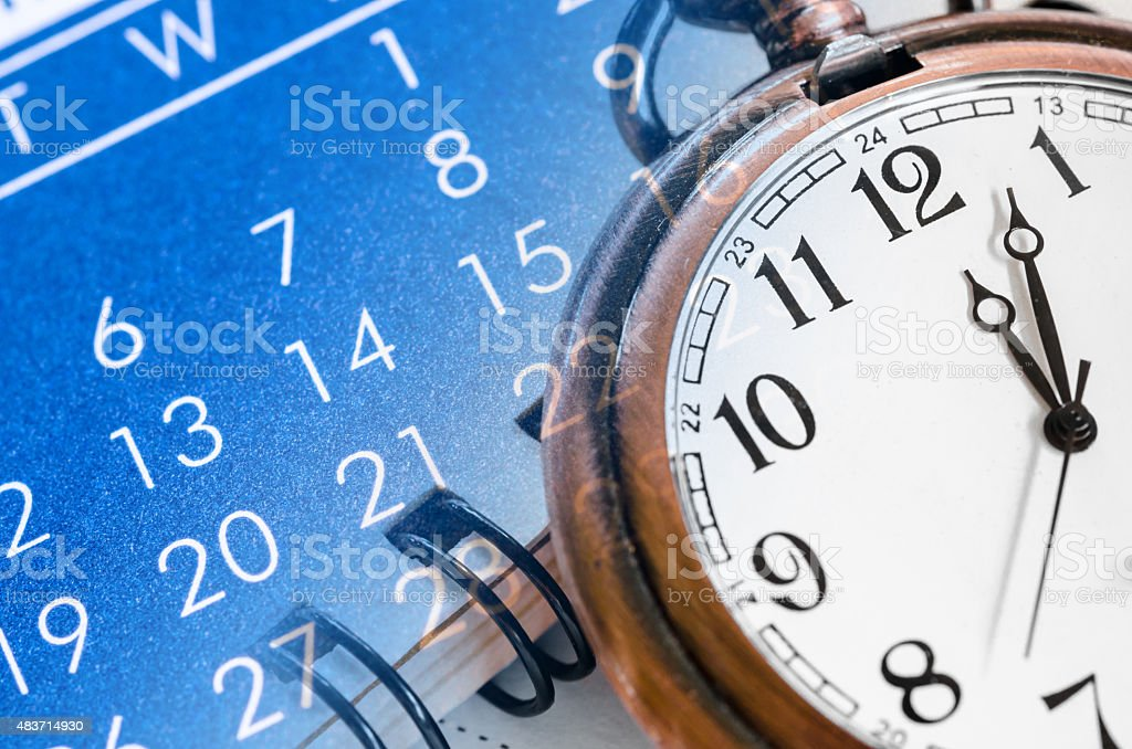 Pocket watch and blue calendar. stock photo