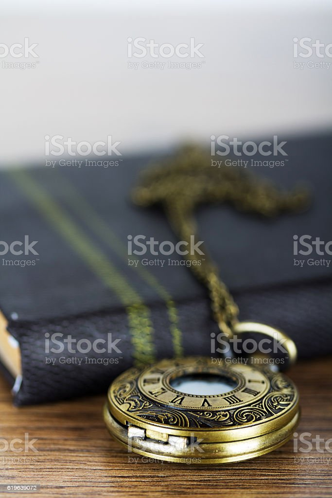 Pocket watch and book against a rustic background stock photo