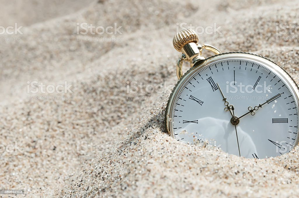 Pocket watch buried in sand stock photo