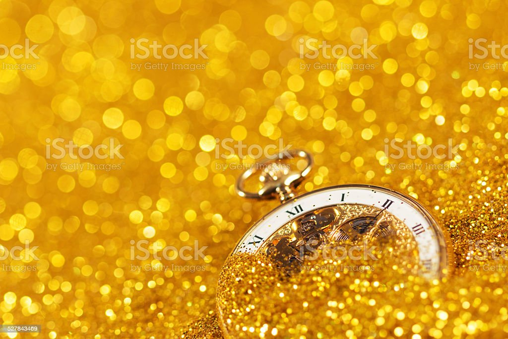 pocket watch half covered by gold sand. stock photo