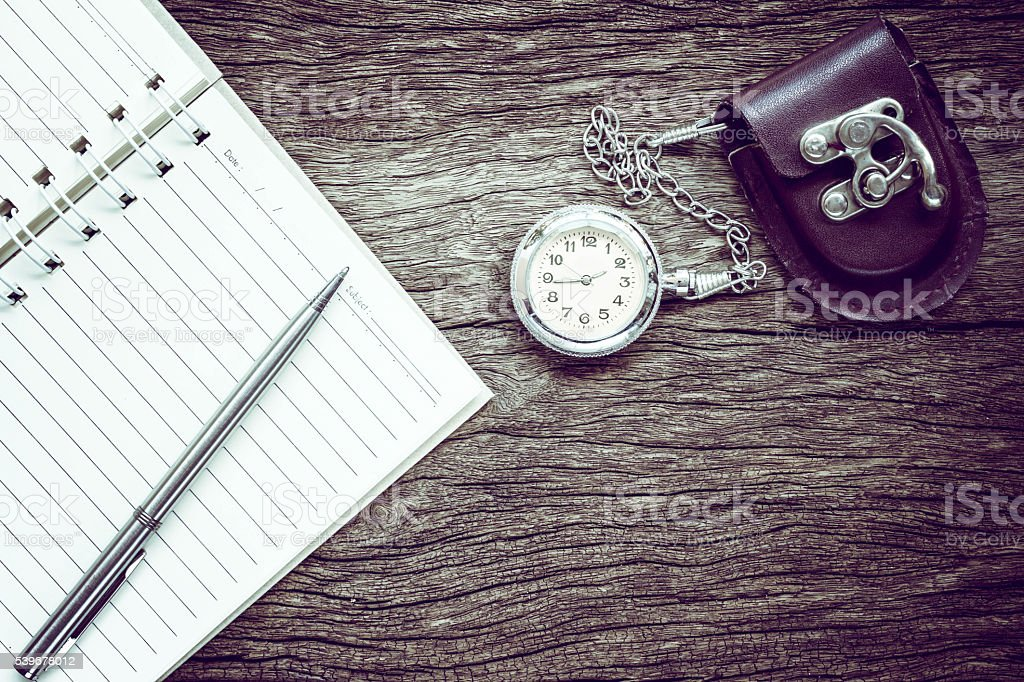 Pocket watch on notebook for notes. stock photo