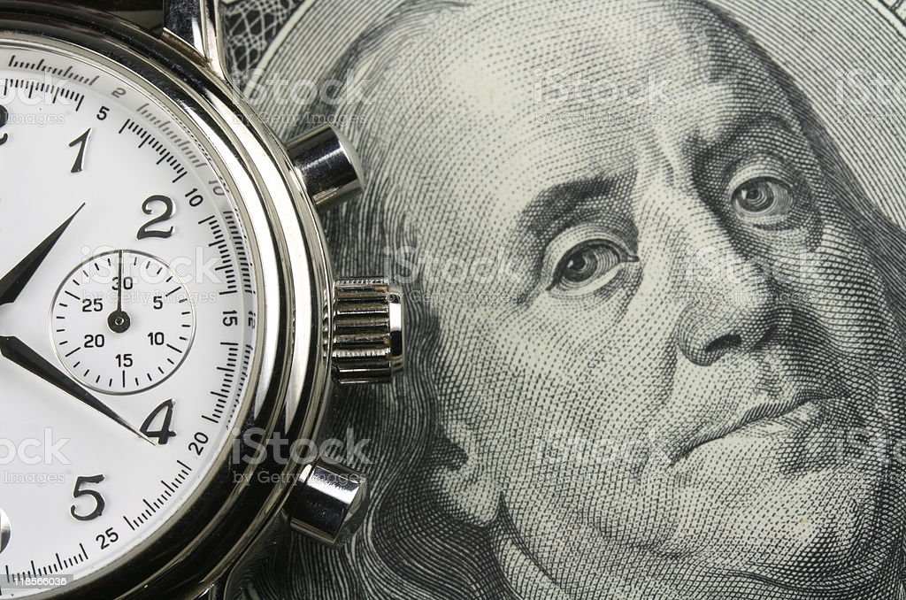 Pocket watch on top of 100 dollar bill stock photo