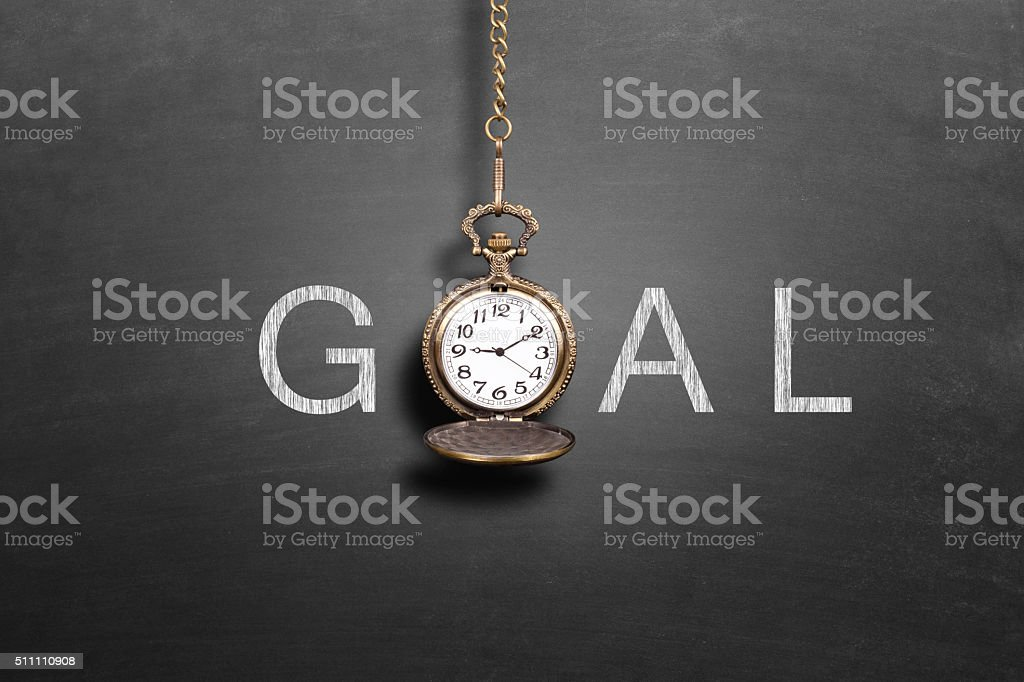 Pocket watch with a chain hanging in front of goal stock photo