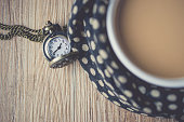 pocket watch with coffee cup wrapped in a scarf