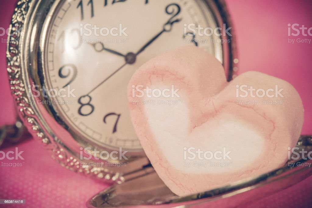 pocket watch with sweet marshmallow candies stock photo