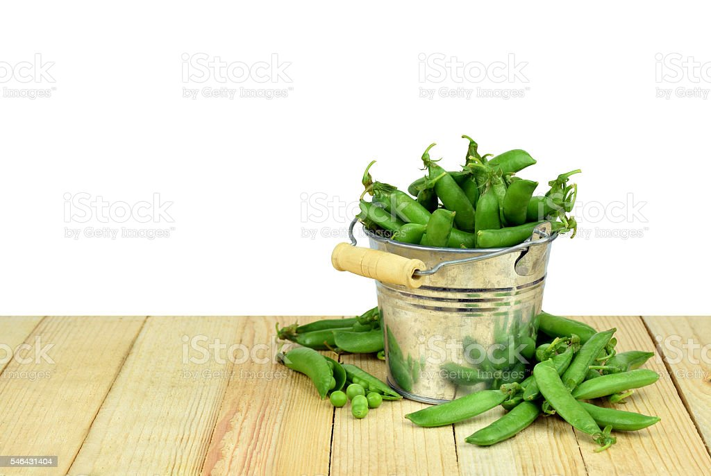 Pods of green peas in a bucket. Isolated. stock photo