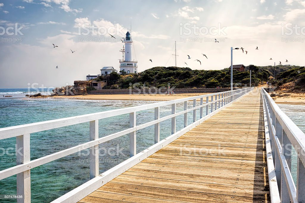 Point Lonsdale Lighthouse and jetty with seagulls in sky stock photo