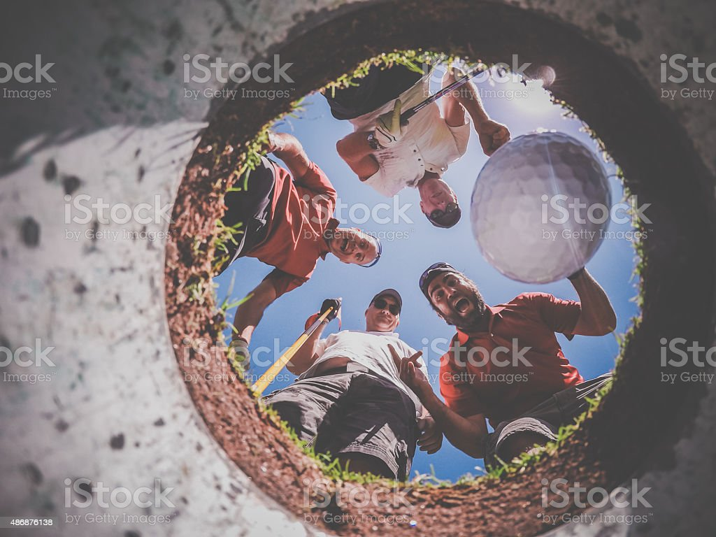 Point Of View Golf Players and Ball From Inside Hole stock photo