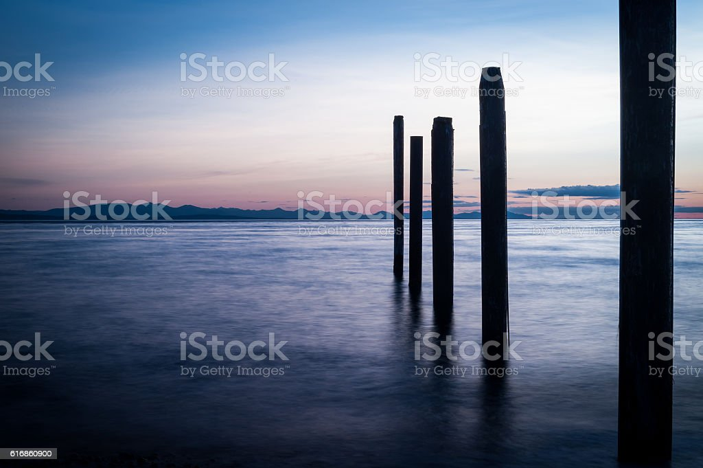 Point Roberts pilings and silky water at night time stock photo
