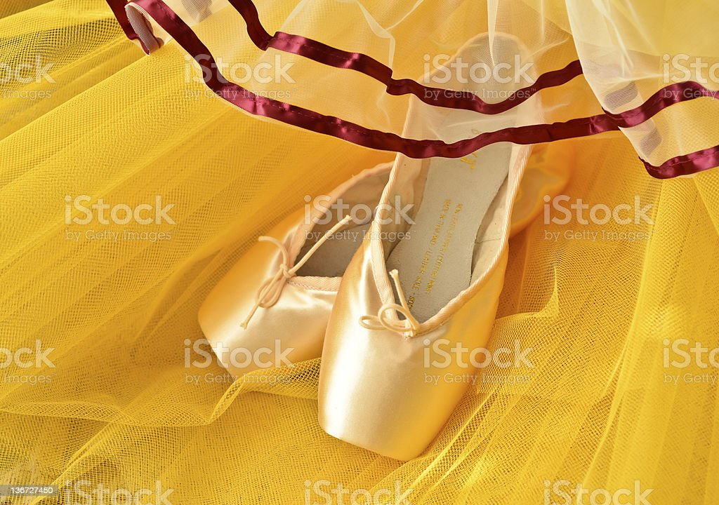 Pointe shoes and yellow tutu stock photo