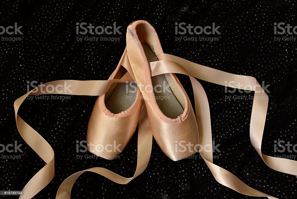 Pointe shoes on sparkling black stock photo