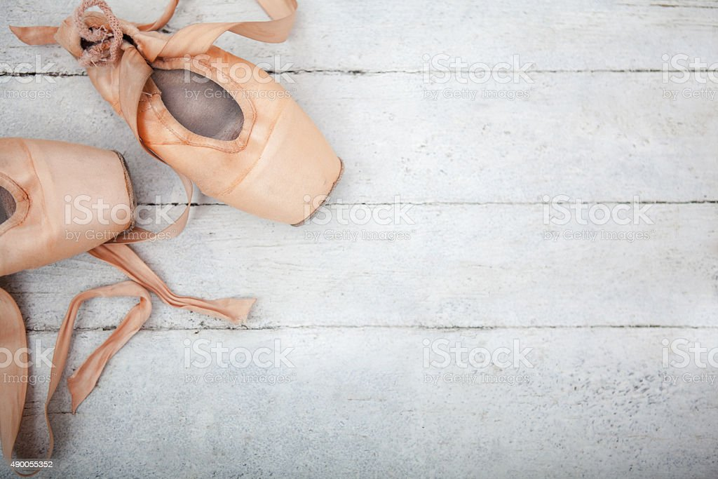 Pointe shoes on wooden background stock photo