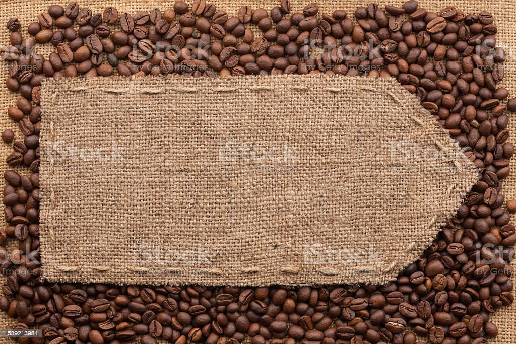 Pointer of burlap lying on a coffee beans background stock photo