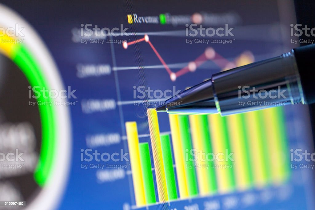 Pointing a Detail on Business Graph at Computer Screen stock photo