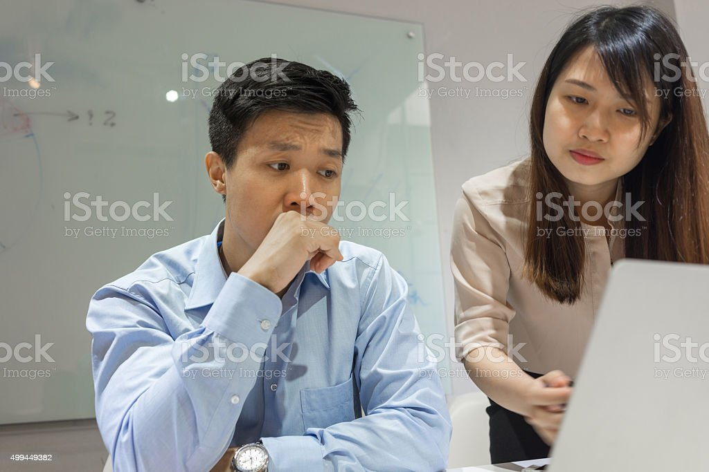 Pointing at laptop screen to show something to her colleague stock photo