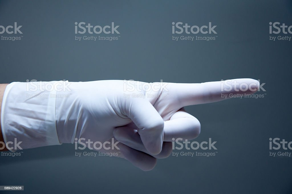 Pointing hand in medical glove stock photo