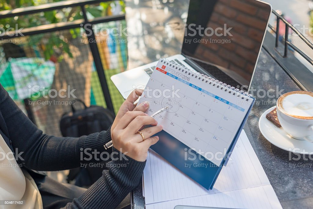 Pointing on calendar by pen to remind about the meeting stock photo