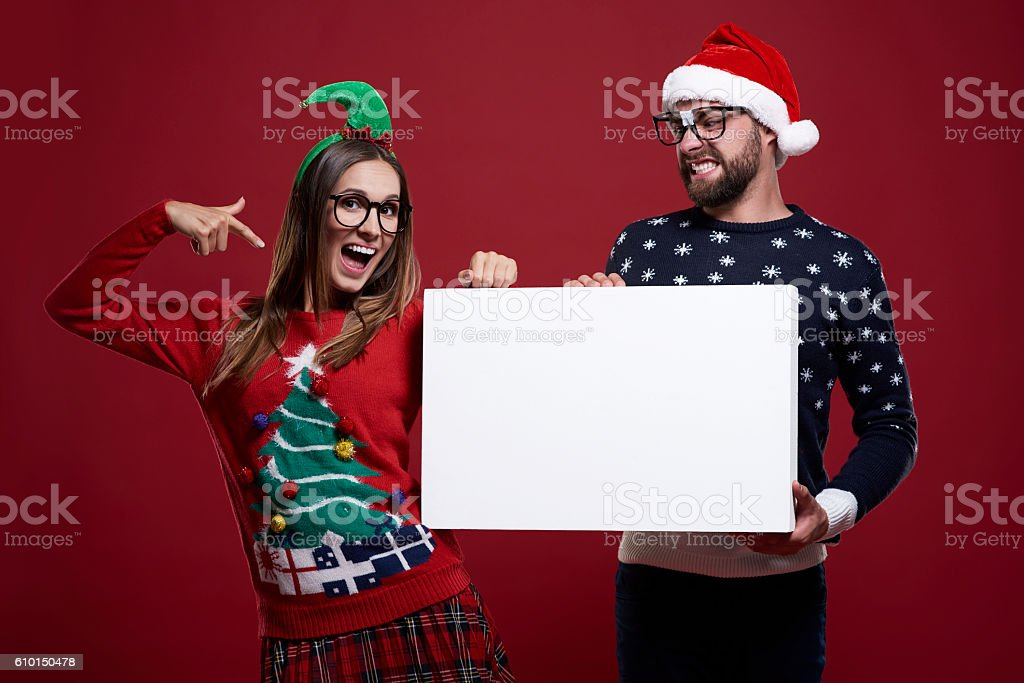 Pointing on placard in christmas clothes stock photo