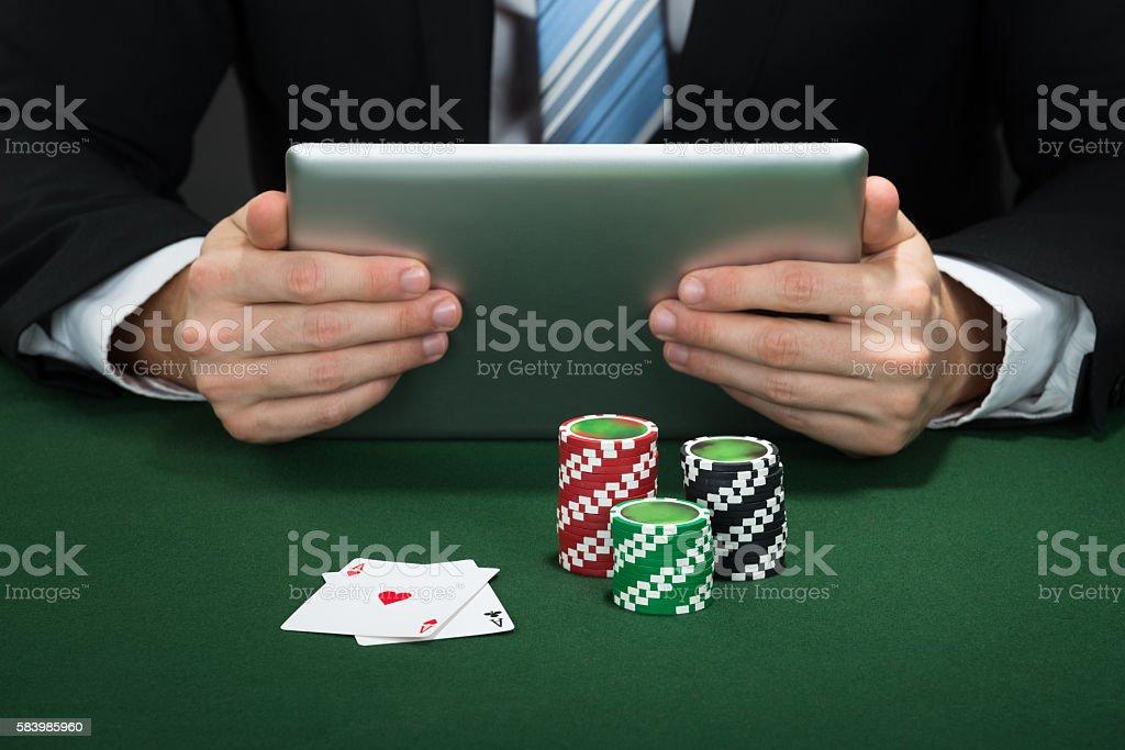 Poker Hand Holding Digital Tablet stock photo
