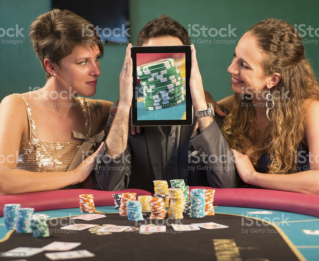 Poker Player Covering his Face with Chips in Digital Table. royalty-free stock photo