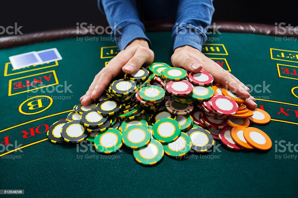 Poker player going all-in pushing his chips forward stock photo