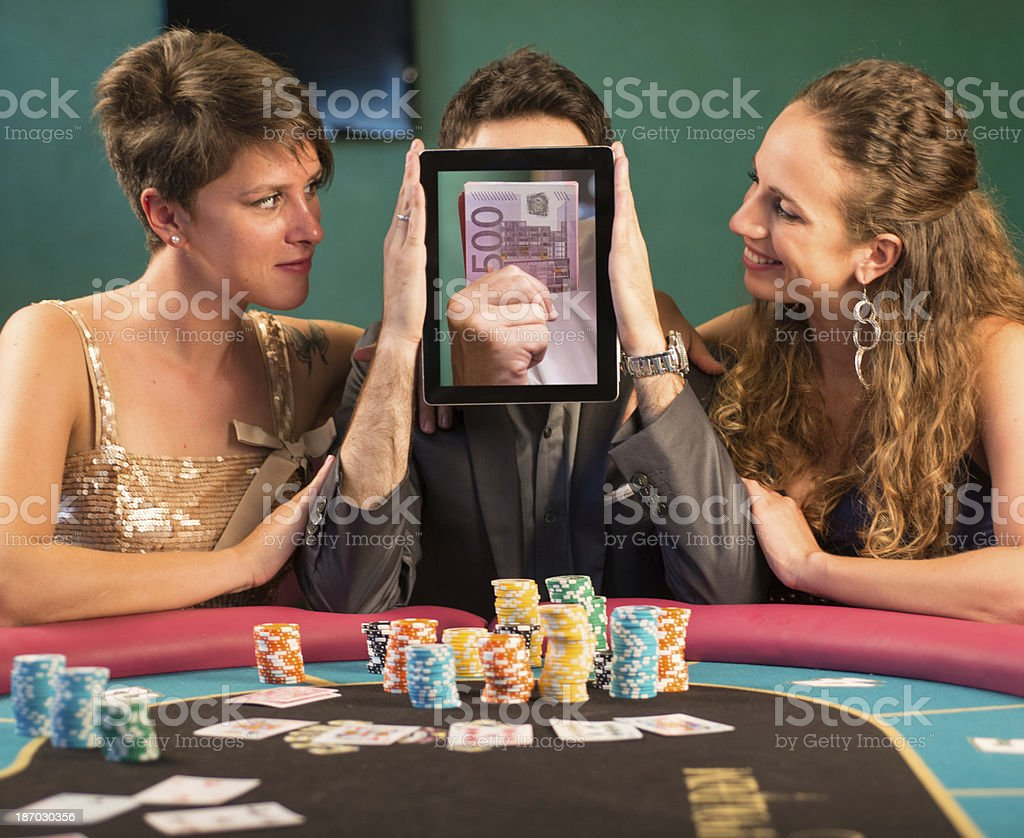 Poker Player Hiding his Face with 500 Euro Bills in a Digital Tablet royalty-free stock photo