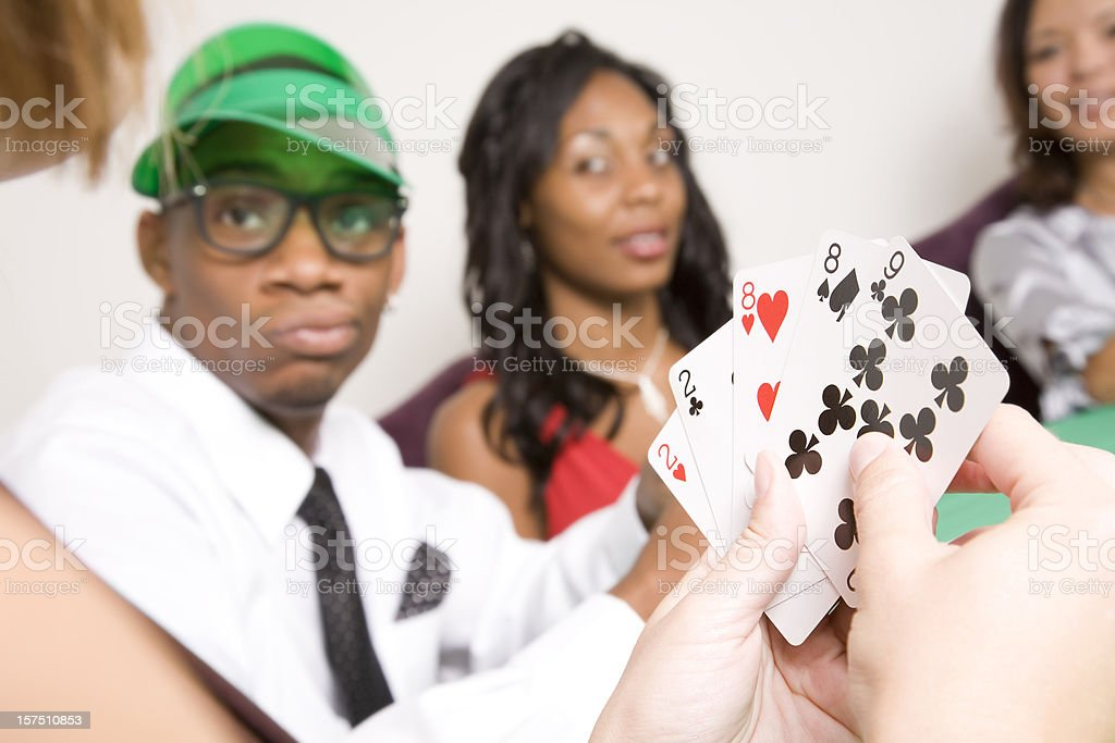 Poker Player Holding a Full House with other players watching royalty-free stock photo