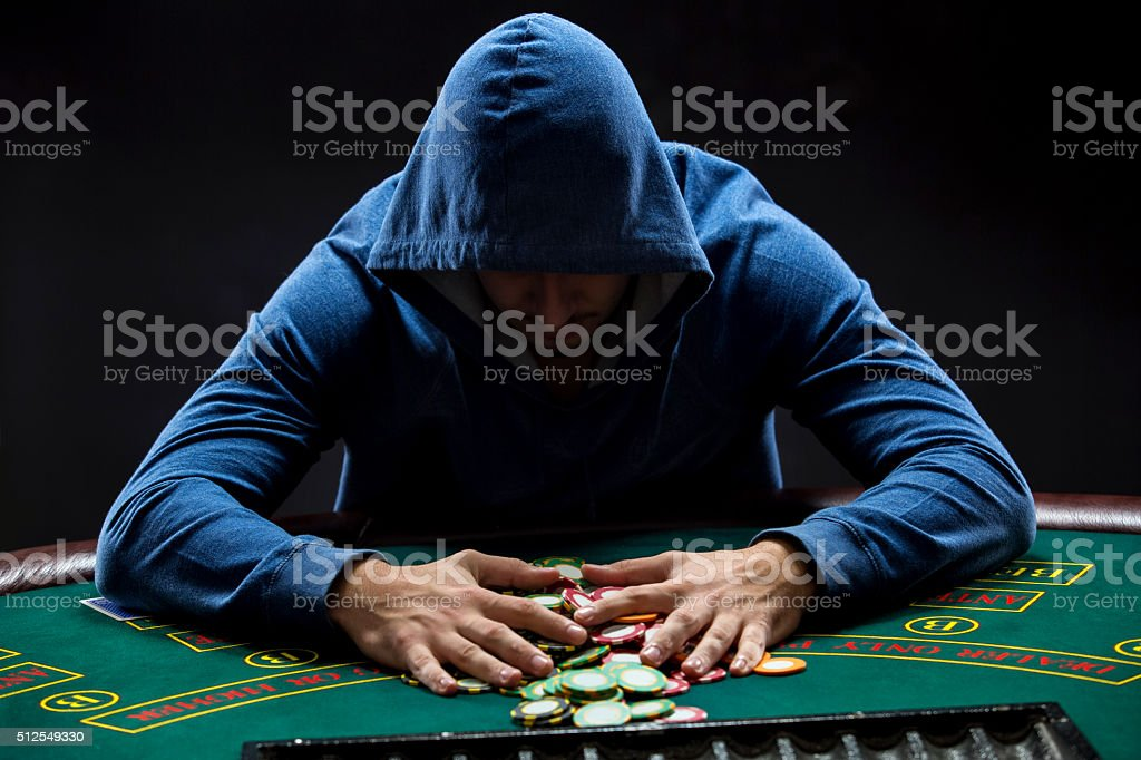 Poker player taking poker chips after winning stock photo