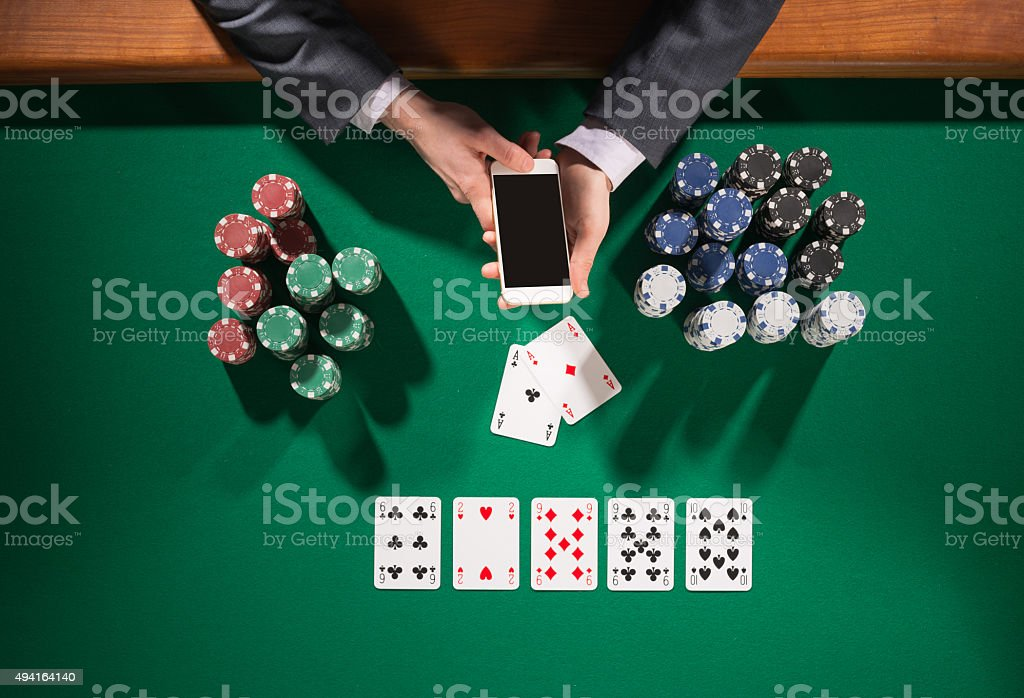 Poker player with smartphone stock photo