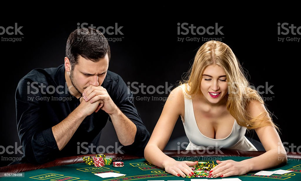 Poker players sitting at poker table and going all-in stock photo