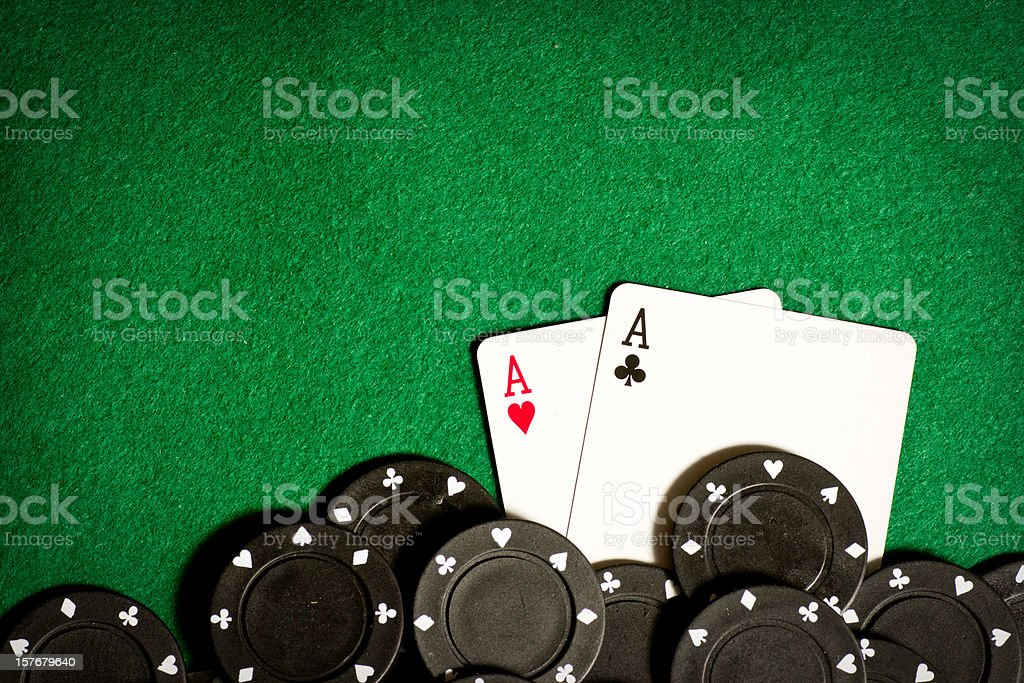 Poker table with black gambling chips and aces stock photo