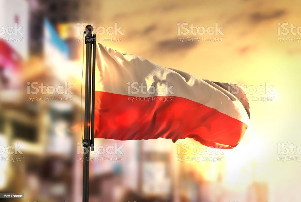 Poland Flag Against City Blurred Background At Sunrise Backlight stock photo