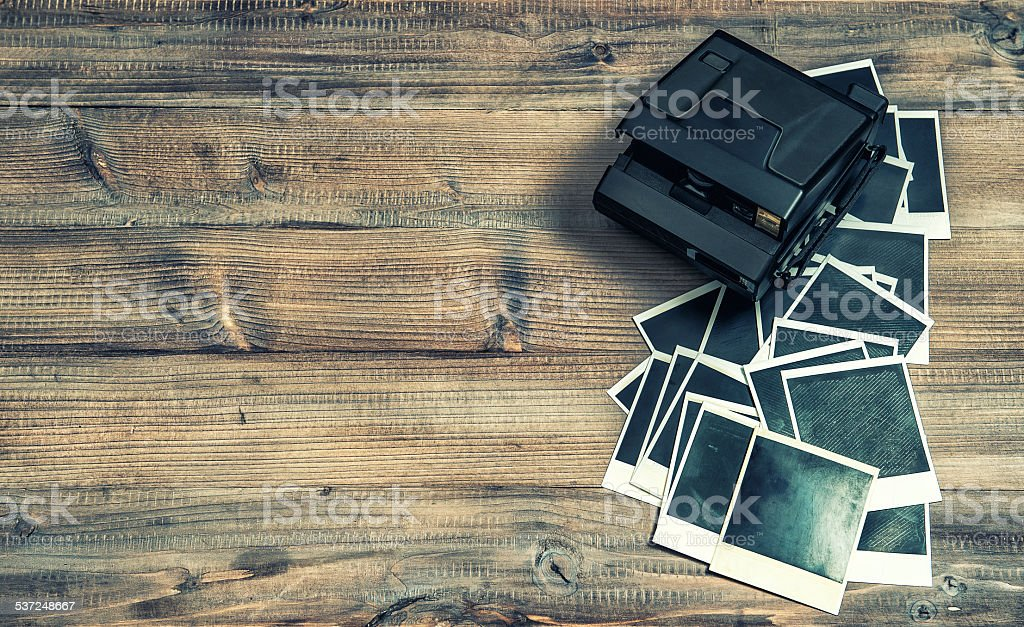 Polaroid photo frames and camera on rustic wooden background stock photo