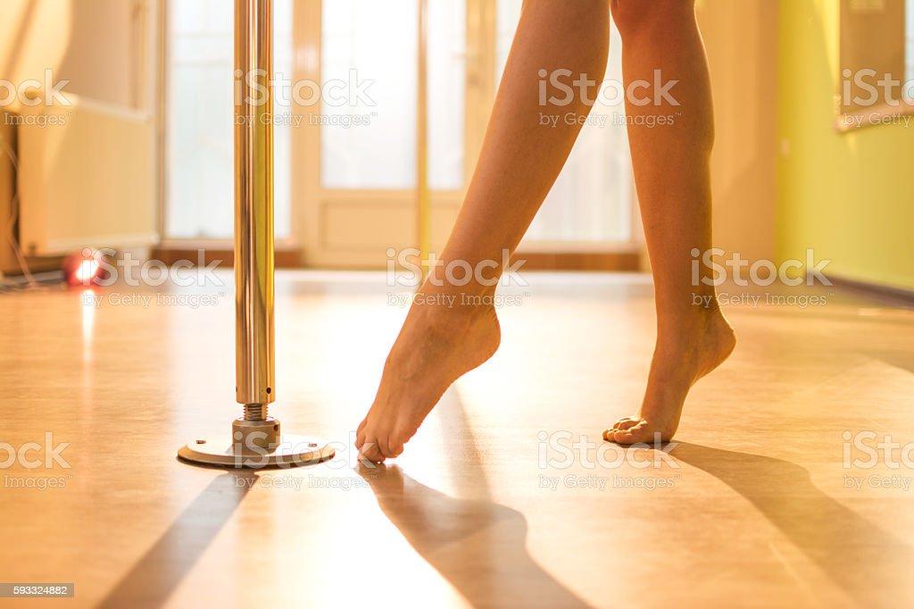 Pole dance. Slender nude female legs in dance studio. stock photo