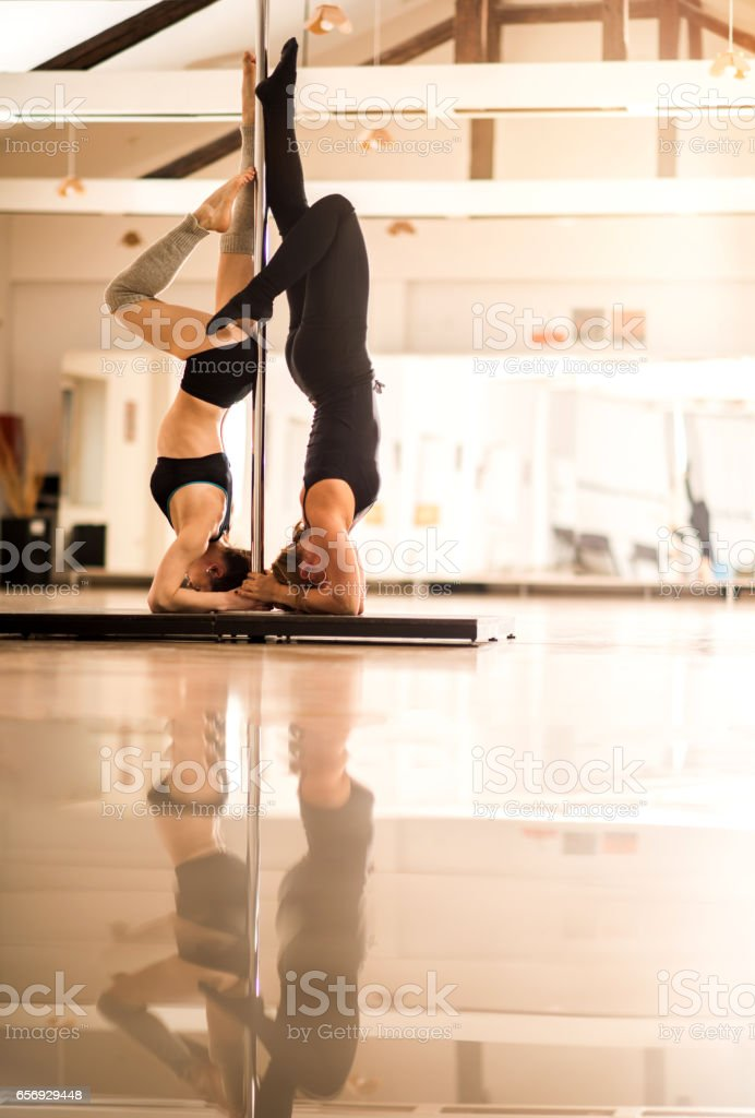 Pole dancers doing a headstand in a studio. stock photo