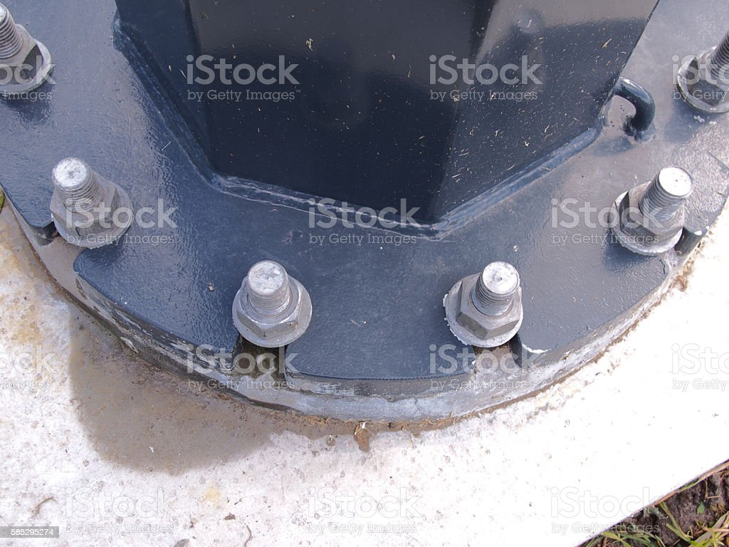 Pole flange with threaded studs on a concrete footing stock photo