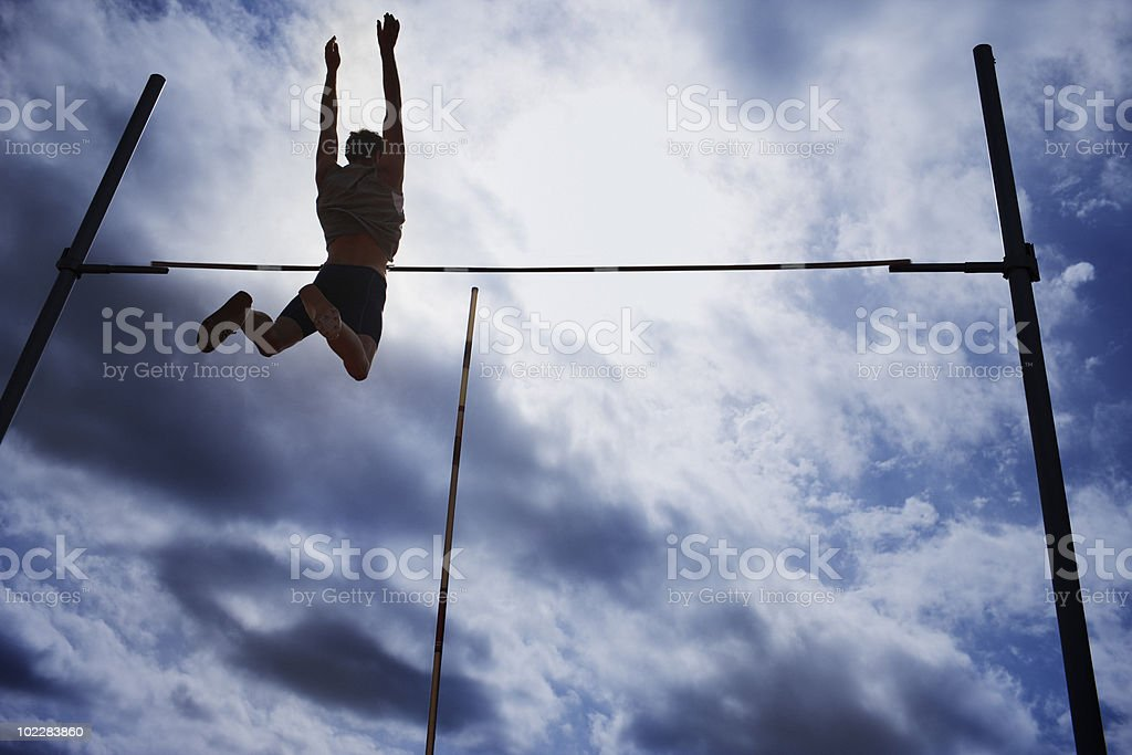 Pole vaulter in mid-air royalty-free stock photo