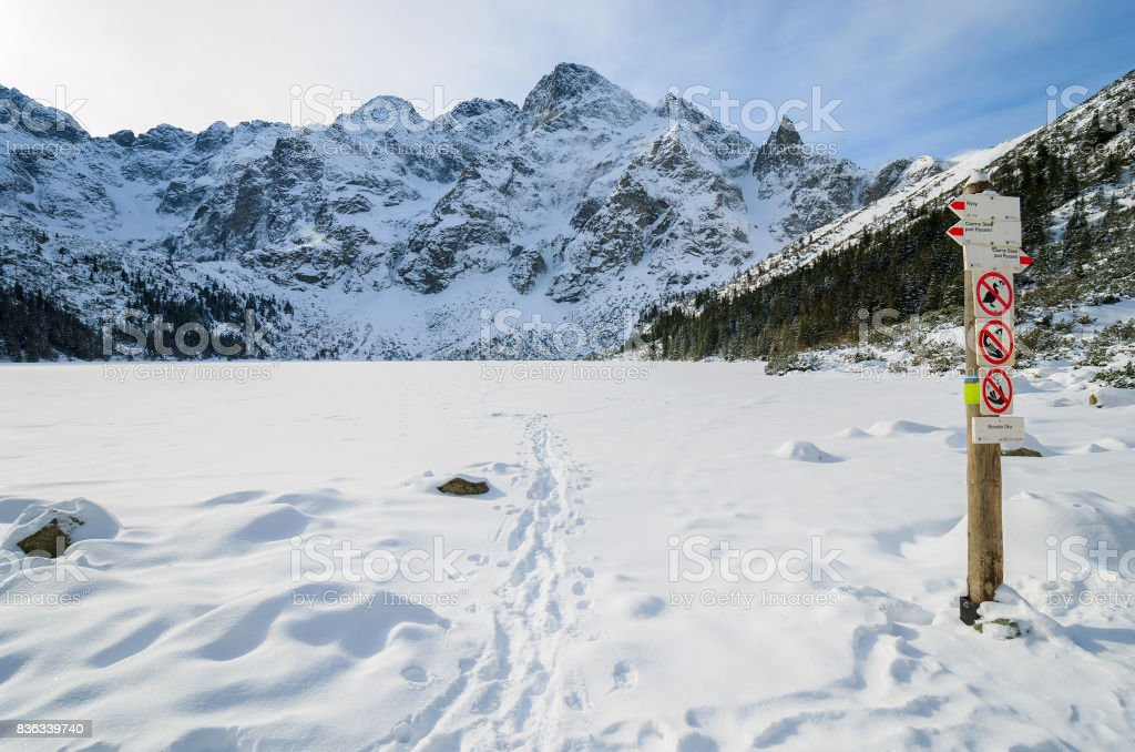 Pole with direction signs and walking time with covered with snow beautiful Morskie Oko lake in winter, High Tatra Mountains, Poland stock photo