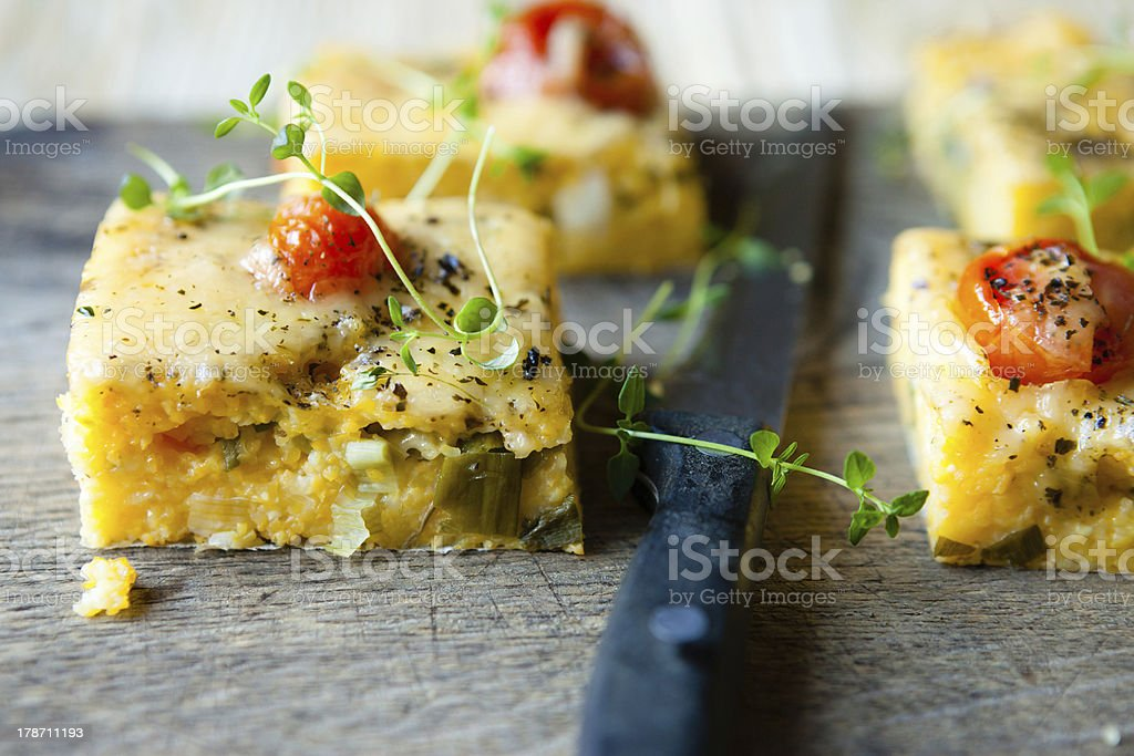 polenta with tomato pieces on the board stock photo